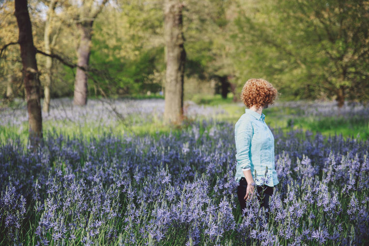 Beauty In Nature Blonde Blubells Blue Jeans Bluebell Casual Clothing Curly Hair Day Field Focus On Foreground Full Length Girl Grass Growth Leisure Activity Lifestyles Nature Nature Park Plant Rear View Shirt Spring Tranquility Tree