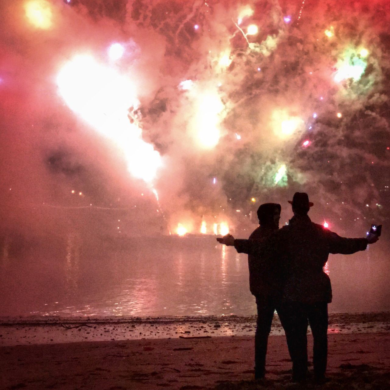 real people, night, firework display, silhouette, firework - man made object, water, standing, smoke - physical structure, men, celebration, arts culture and entertainment, outdoors, event, illuminated, lifestyles, firework, sky, leisure activity, sea, two people, togetherness, nature, people