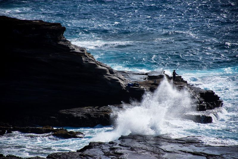 High angle view of waves splashing on rocks