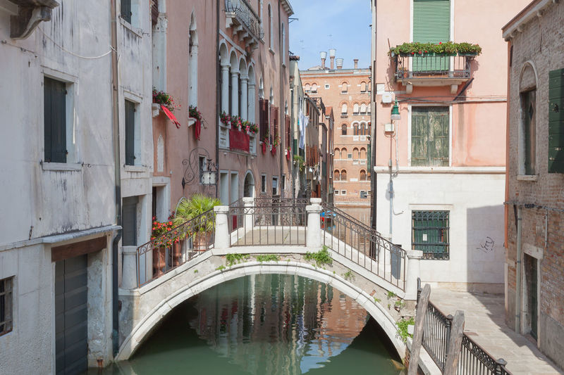 Arch bridge over canal amidst buildings in city