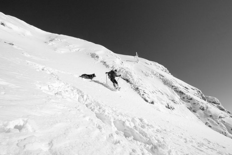 Low angle view of senior man skiing on snow covered mountain against sky