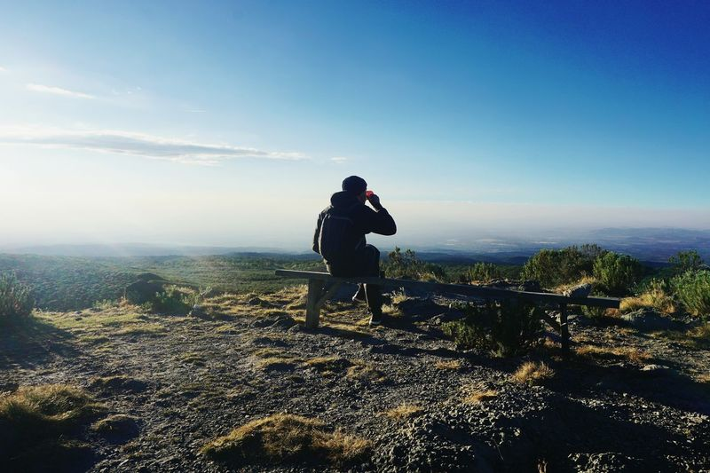 Rear view of man having drink while sitting on bench at mountain against sky
