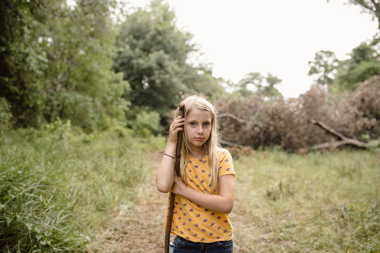 Portrait of cute girl holding stick while standing on land in forest
