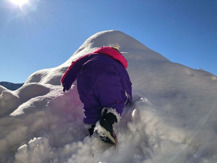 Low Angle View Of Boy On Snow Against Sky