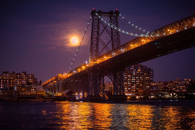 Low angle view of williamsburg bridge over east river at night