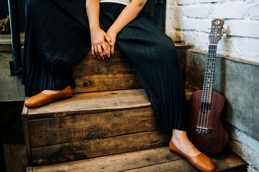 Adult Arts Culture And Entertainment Guitar Hand Human Body Part Human Leg Low Section Men Midsection Music Musical Equipment Musical Instrument One Person Playing Real People Sitting String Instrument Women Wood - Material