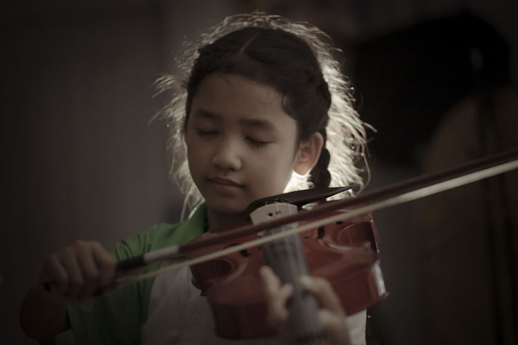 Girl playing violin indoors