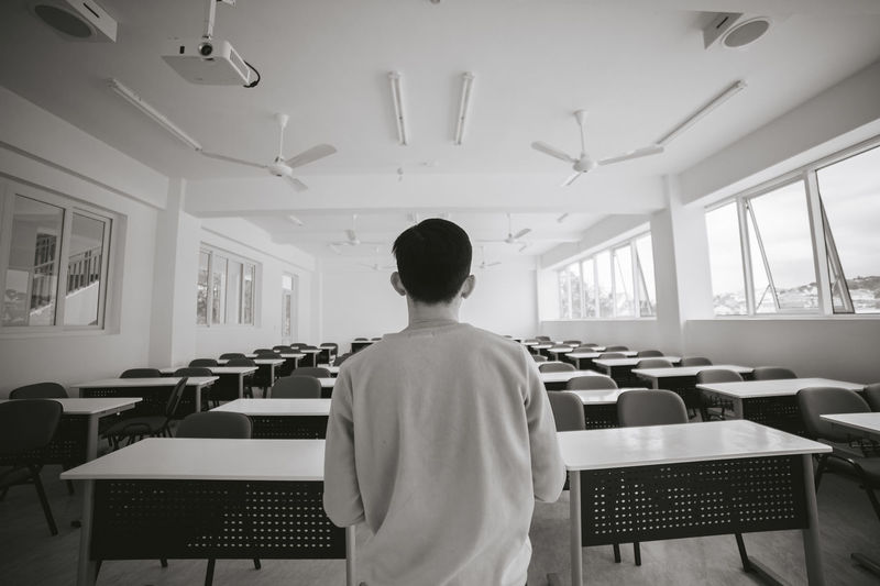 Rear view of man sitting table in classroom