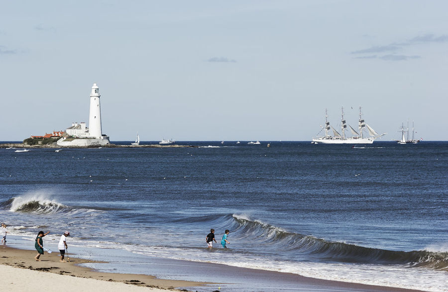 Summer family fun on Whitley Bay beach while a tall ship sails past St Marys lighthouse Beach Coast Coastline Day Fun Leisure Activity Lighthouse North Sea Northumberland Outdoors Relaxation Sand Scenics Sea Seaside Shore St Marys Lighthouse Summer Tall Ship Tourism Vacations Waves