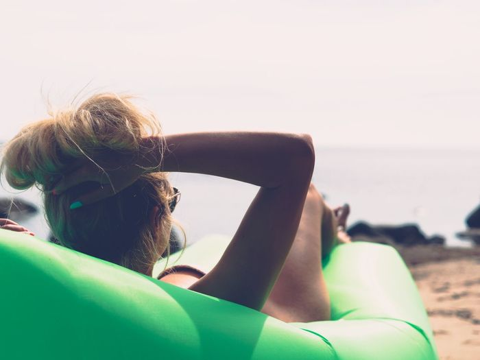 Rear view of sensuous woman relaxing on inflatable chair at beach