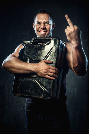 Man with metal fuel can showing middle finger Benzine Container FuckYou Fuel Gas Gasoline Man Masculinity Adult Canister Energy Flammable Fuel Can Fuel Tank Jerry Jerrycan Men Muscle Muscular Build Oil One Man Only One Person People Petrol Strength