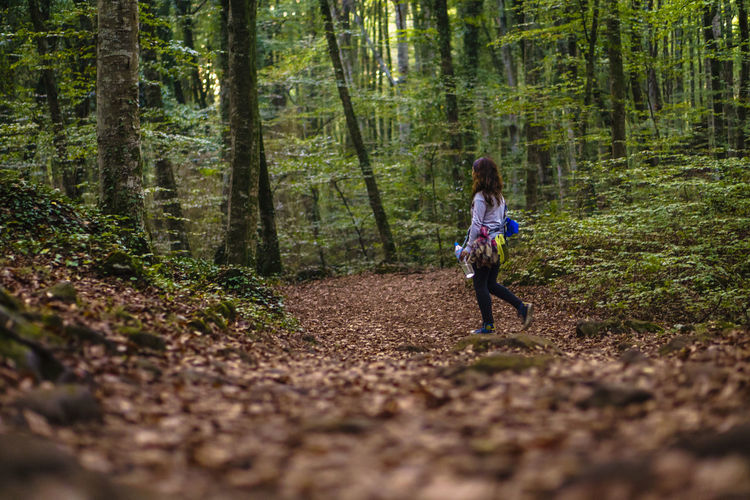 Rear view of woman running on road amidst trees in forest