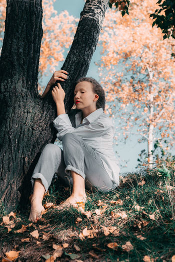 Full length of young woman on tree trunk during autumn