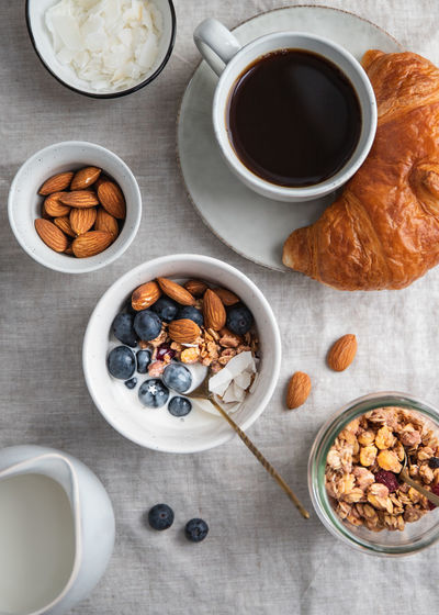 Top view of breakfast table with coffee, croissant, granola, nuts, berries and milk. Flat lay, healthy eating concept. Granola Food Breakfast Bowl Blueberry Berry Porridge Table Concept Top Flat Lay Ceramics Cereal Lifestyle Meal Holding Cotton Girl Vegan Oat Almond Chia Nuts Croissant Milk Directly  Above Two Juice Dessert Espresso Vegetarian Natural Organic Snack Sweet Muesli Yogurt View Background Seed Photography Food And Drink
