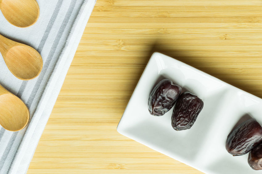 Dates or kurma in white plate over wooden background Close-up Dates Fasting Food Freshness Kurma Muslim No People Ramadhan Top View