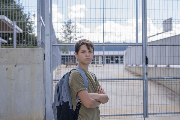 Portrait of confident boy with arms crossed standing against metal gate