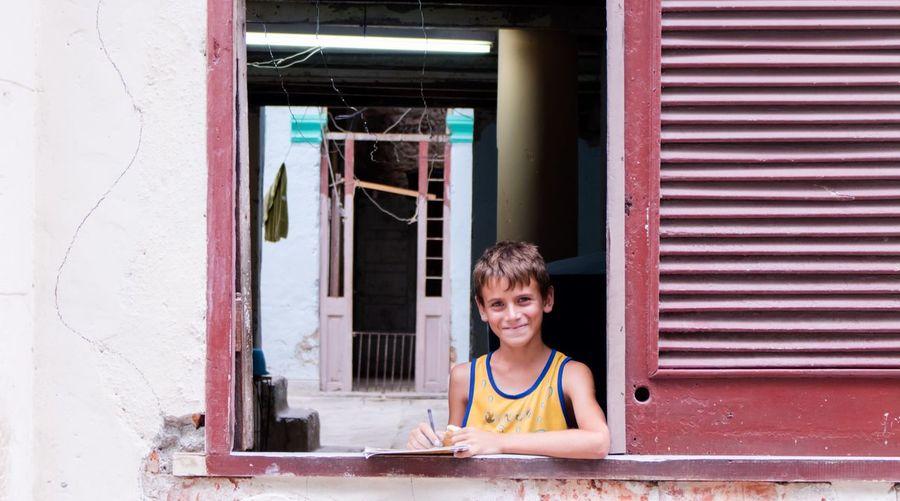 Portrait of smiling boy sitting on window