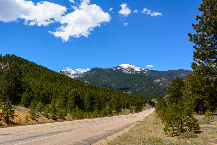 Colorado landscape with the Rocky Mountains in the background. Colorado Estes Park, CO Rocky Mountains USA The Week On EyeEm USA Beauty In Nature Blue Sky Day Forest Landscape Mountain Mountain Range Nature No People Outdoors Road Scenics Sky Tranquility Tree