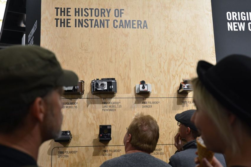 Camera On The Wall Camera Equipment Impossible Project Photokina Focus On Background People Watching Camera - Photographic Equipment Cameras Photography TakeoverContrast Instant Photography