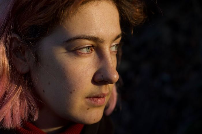 Close-up of thoughtful beautiful woman looking away during sunset