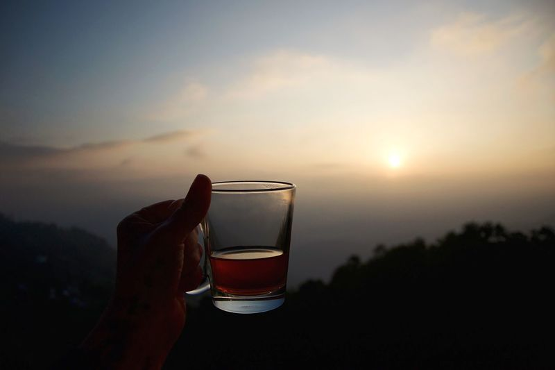 Close-up of hand holding beer glass against sky during sunset