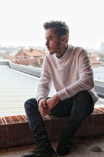 Full length of man sitting on roof against sky
