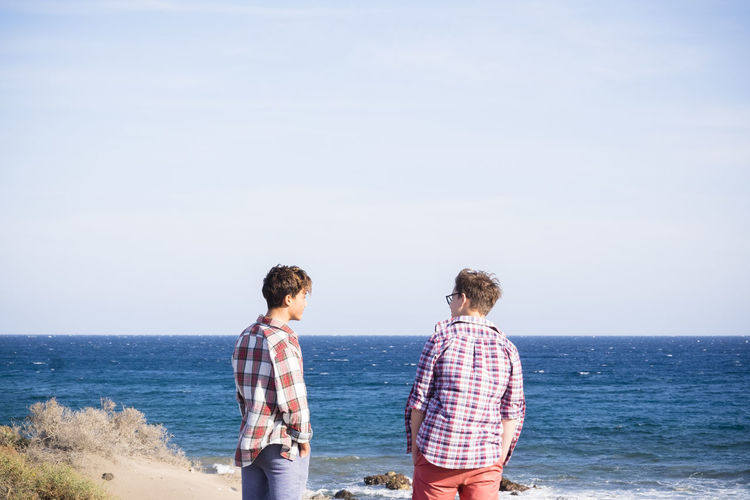 Rear view of friends standing against sea and sky