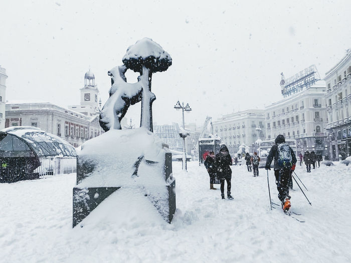People walking on snow covered buildings in city