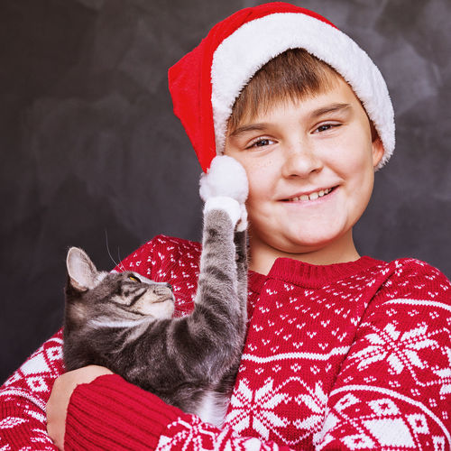 Animal Themes Boys Cap Childhood Christmas Close-up Cute Day Domestic Animals Indoors  Lifestyles Looking At Camera Mammal One Animal One Person People Pets Portrait Real People Red Santa Hat Warm Clothing