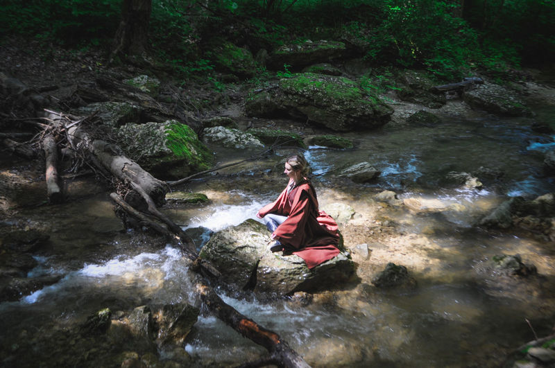 Man sitting on rock by river in forest