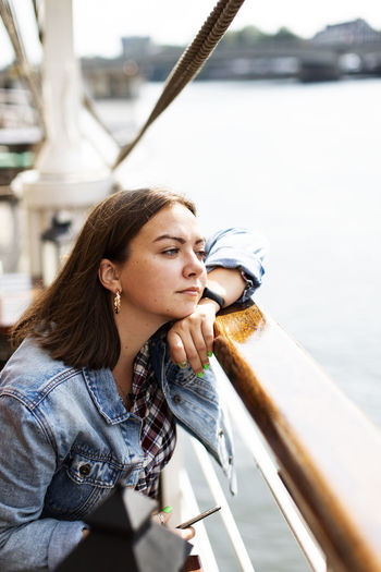 Young woman looking away while sitting on boat in sea