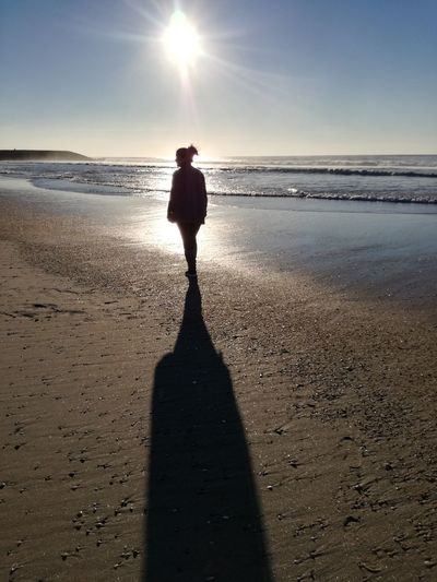 Silhouette woman standing on shore at beach against sky