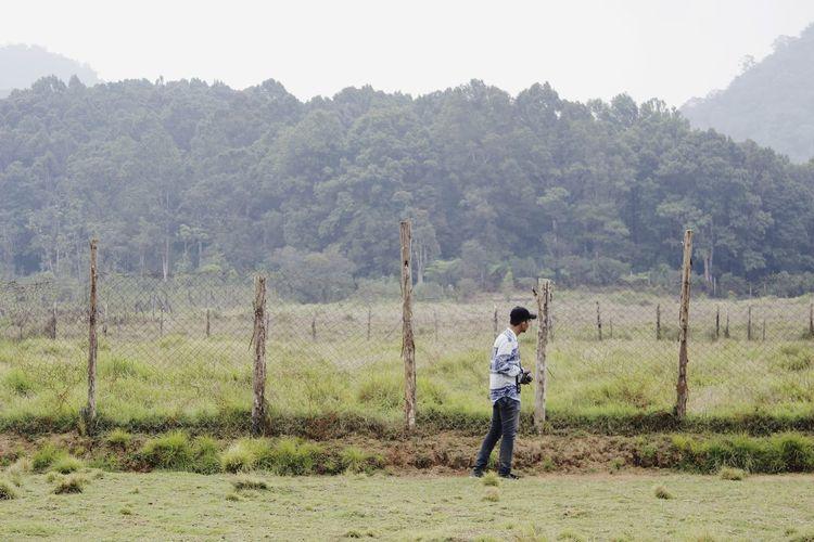 Full length of boy standing on field against sky