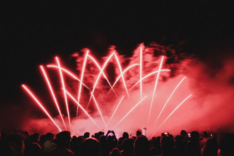 Crowd looking at firework display during night