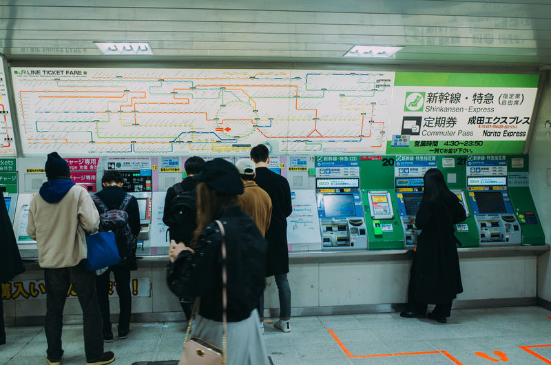Rear view of people walking in subway station