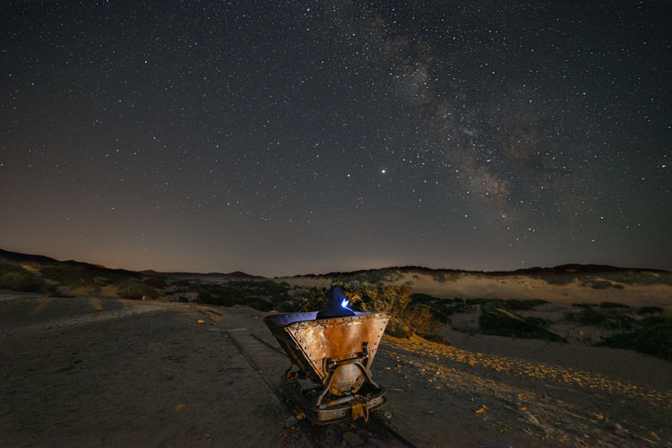 Old rusty minerali carriera on land against star field at night