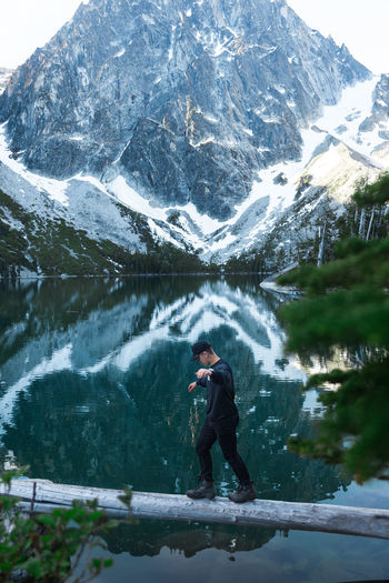 Full length of man standing on tree trunk against snowcapped mountain