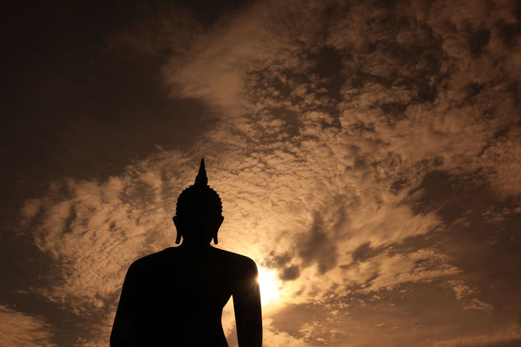 Low angle view of silhouette buddha statue against sky during sunset