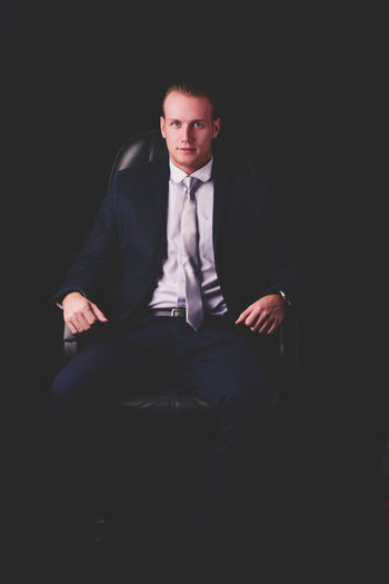 Portrait of businessman sitting on chair against black background