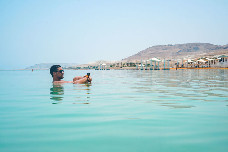 The Dead Sea, Israel Adult Beauty In Nature Clear Sky Copy Space Day Leisure Activity Lifestyles Men Nature One Person Outdoors Real People Sea Shirtless Sky Swimming Swimming Pool The Dead Sea Trip Water Waterfront