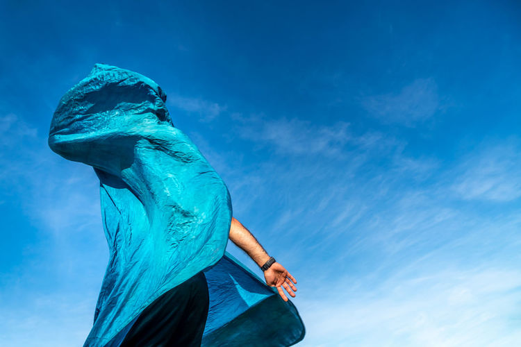 Low Angle View Of Man Covered With Scarf Against Sky