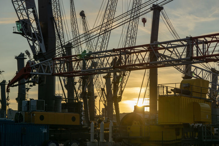 cranes in the harbor of rostock Architecture Built Structure Machinery Nature Industry Transportation Connection Construction Site Metal Development Low Angle View Mode Of Transportation Construction Industry Crane - Construction Machinery Outdoors Construction Equipment Sunlight Sky Complexity Sunset No People Sun