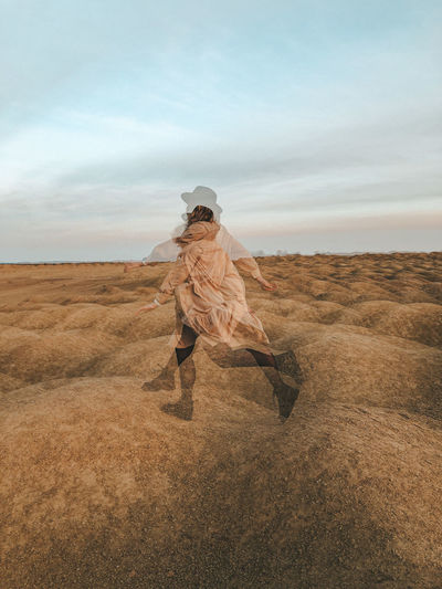 Multiple exposure image of young woman running on field