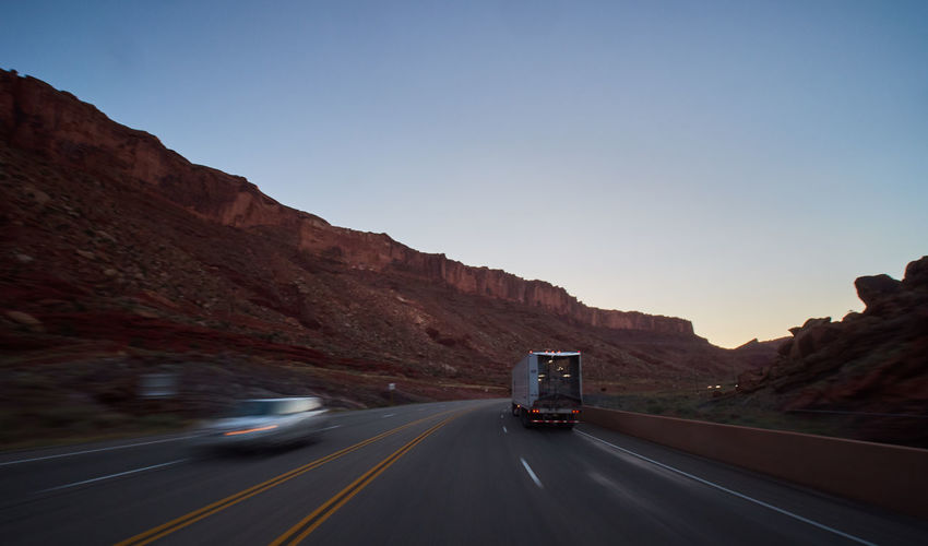 Mountain Road Transportation Land Vehicle Sky Motion Nature Mode Of Transportation The Way Forward No People on the move Direction Road Marking Symbol Motor Vehicle Day Marking Blurred Motion Clear Sky Beauty In Nature Mountain Range Outdoors Formation