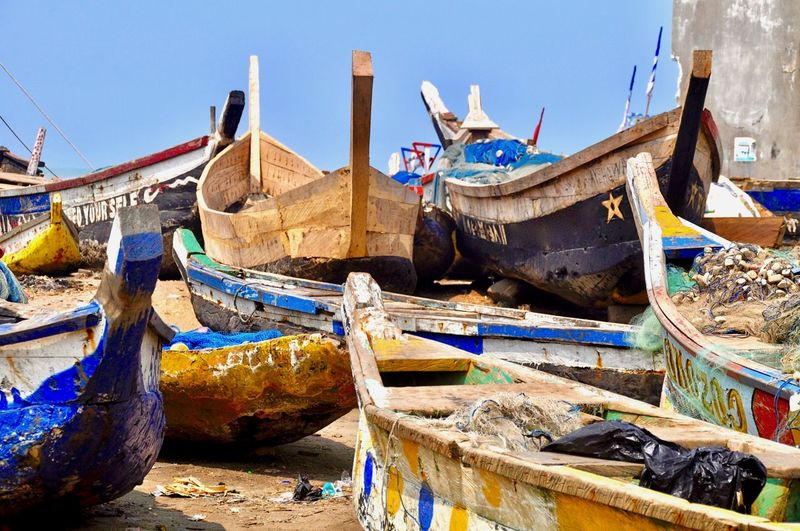 Fishing boats moored at beach against sky