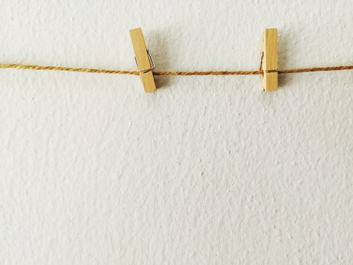 Close-up of clothespins on rope against wall
