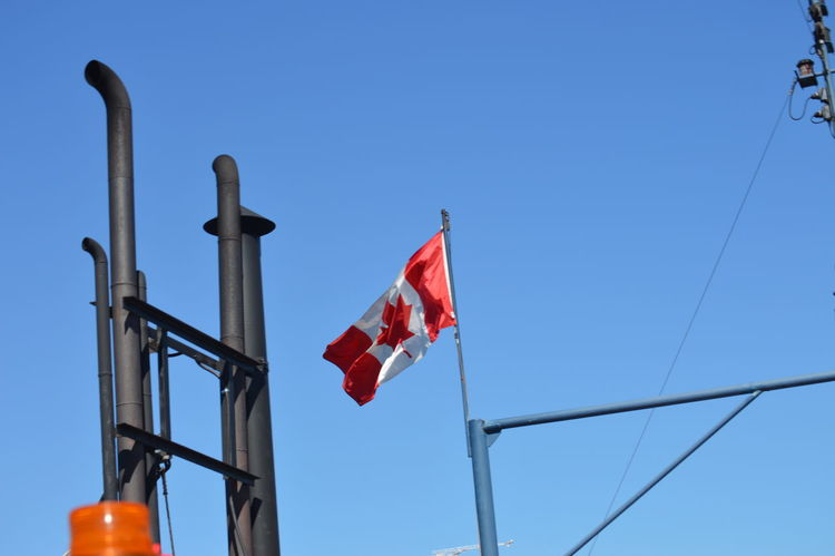 Blue Canada Flag Clear Sky Culture Day Flag High Section Identity Low Angle View Multi Colored No People Outdoors Pole Pride Red Sky