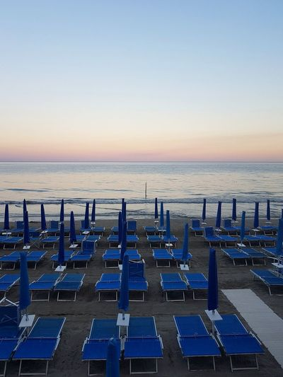 Beach Sea Horizon Over Water Sand Chair Vacations Outdoor Chair Summer Business Finance And Industry Blue Tranquility Outdoors Arrangement Water No People Sky Clear Sky Relaxation Sunset Day Liguria, Italy Vacations Tourist Destination Travel Destinations