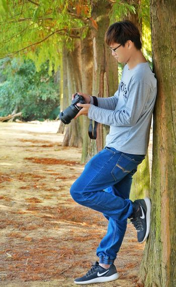 Man Photographing Against Tree In Forest
