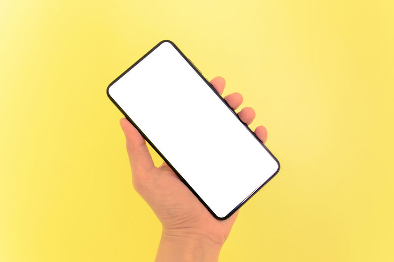 Low section of person holding smart phone against yellow background